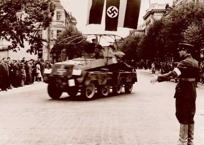 1941 m. birželio pabaigoje lietuviai patys išsikovojo laisvę, atkūrė tarpukario įstaigas ir palaikė tvarką krašte. Lietuvių policininkas rodo vokiečių kariuomenės šarvuočio įgulai kelią, kuriuo ji turi važiuoti.