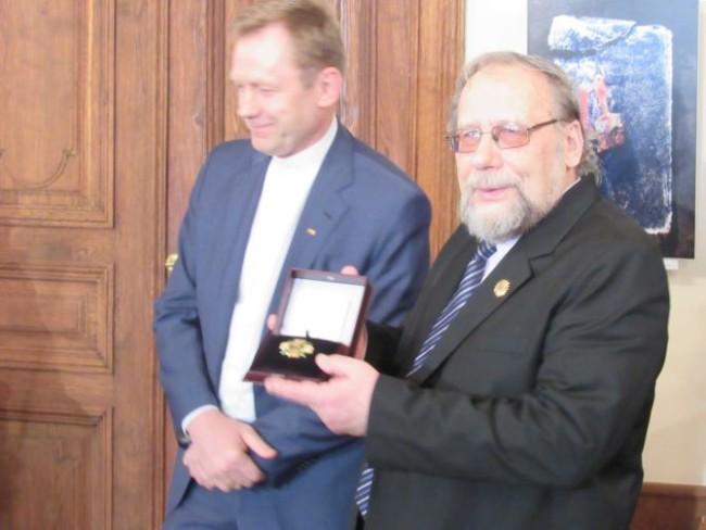 """Perlio VAISIETOS nuotraukoje: aukso garbės ženklą """"Nešk savo šviesą ir tikėk"""" rašytojui, redaktoriui ir visuomenės veikėjui Leonui Peleckiui-Kaktavičiui įteikus."""